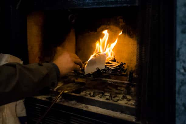 burning paper in fireplace